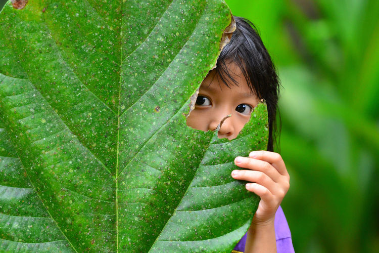 Close-up of girl hiding her face behind leaf