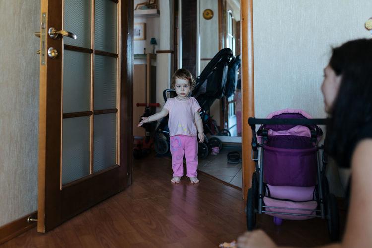 Rear view of women standing on door at home