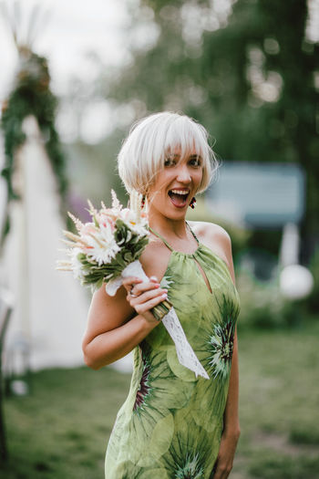 Portrait of smiling woman with bouquet standing against on land