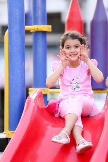 Portrait Of Girl Gesturing While Sitting On Slide At Park