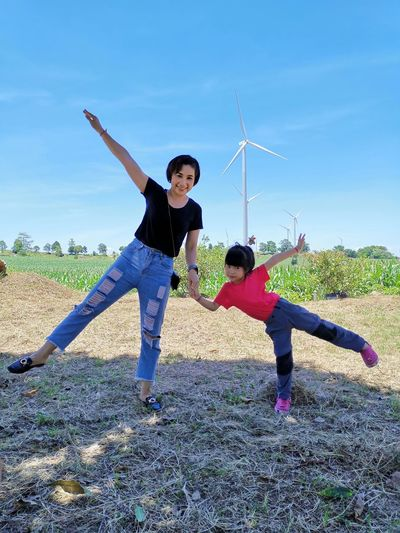 Mother and daughter with arms outstretched standing on grassy land