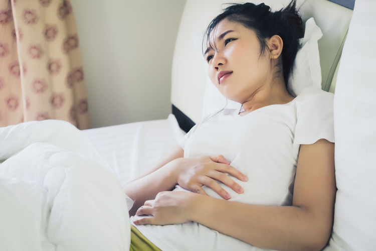 Young woman with hand on stomach in pain lying on bed at home