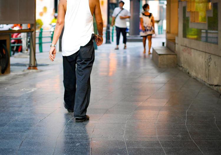 Low section of men walking on sidewalk in city
