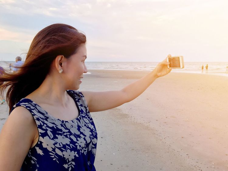 EyeEm Selects A Thai girl is taking selfie on the beach. Beach Sea Sand Water Real People One Person Young Adult Vacations Leisure Activity Outdoors Young Women Nature Day Photography Themes Lifestyles Sky Scenics Beauty In Nature Beautiful Woman Girl Selfie Herself Technology Video Call Multimedia