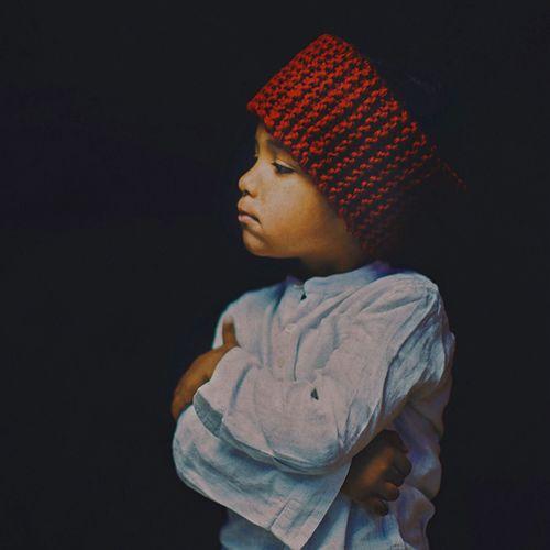 Boy wearing knit hat against black background