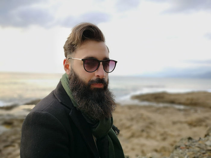 Portrait of bearded man in sunglasses at beach