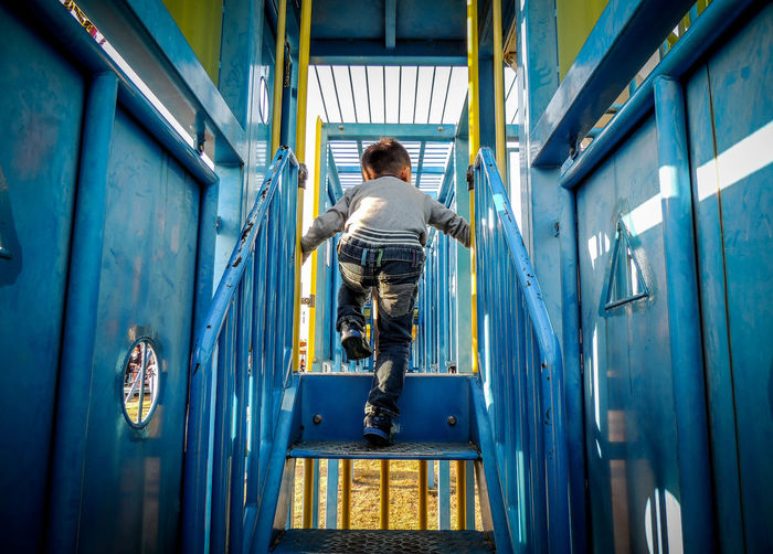 Rear view of boy playing in jungle gym at playground