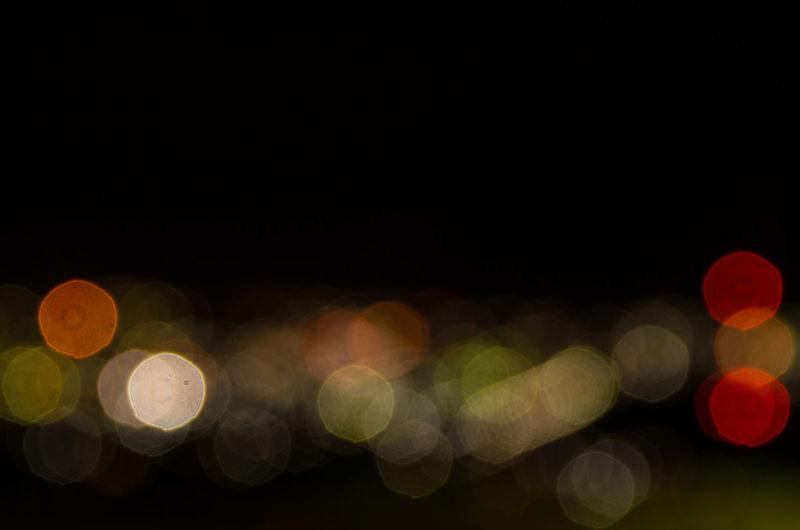 Defocused image of illuminated light bulb against black background