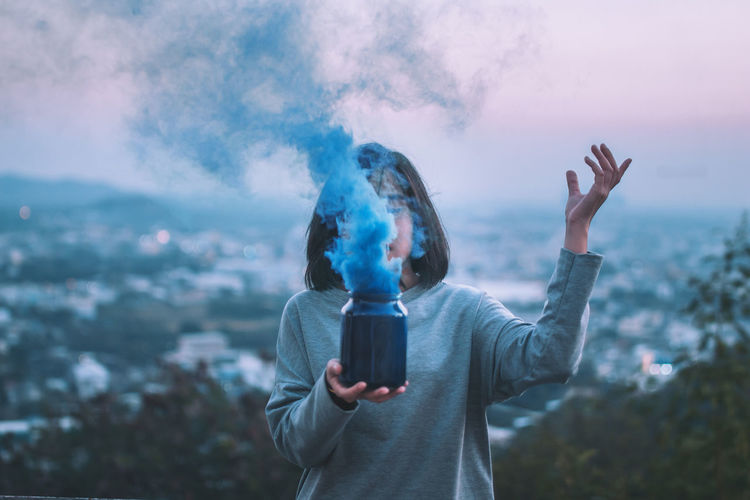 Woman holding container with blue smoke against sky