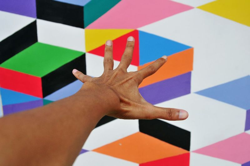 High angle view of human hand against colored wall