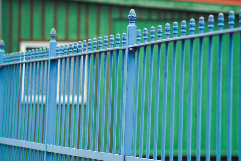 Turquoise Metallic Fence Against Building