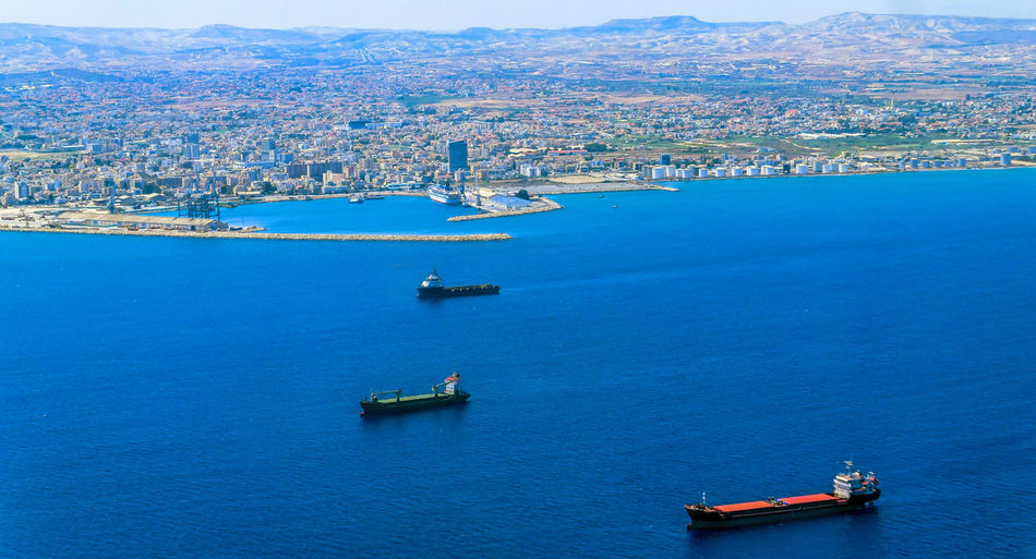 Aerial view of navy ships near coast of sunny Cyprus Larnaca Cyprus Mediterranean  Sea Blue Watet Coast Sunny Cityscape Nautical Vessel City Sea Water Aerial View Industry Blue Urban Skyline Freight Transportation Container Ship Industrial Ship Sailing Ship Nautical Equipment