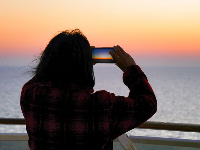 Rear View Of Person Photographing Sea Against Sky During Sunset