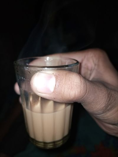 Close-up of hand holding candle against black background