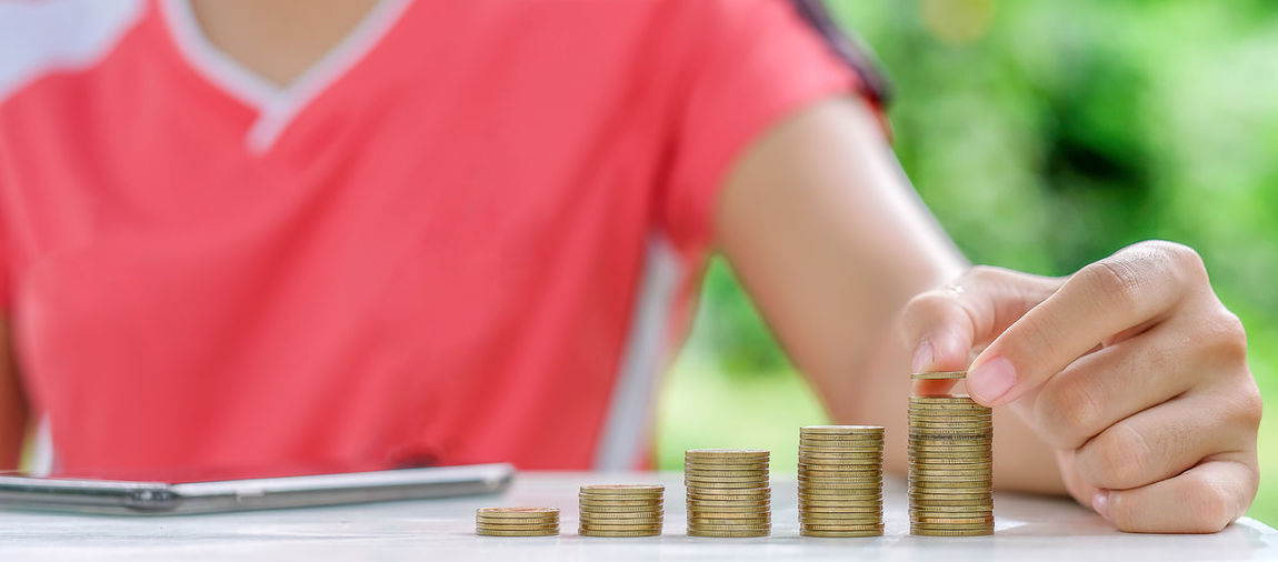 Midsection of woman stacking coins on table