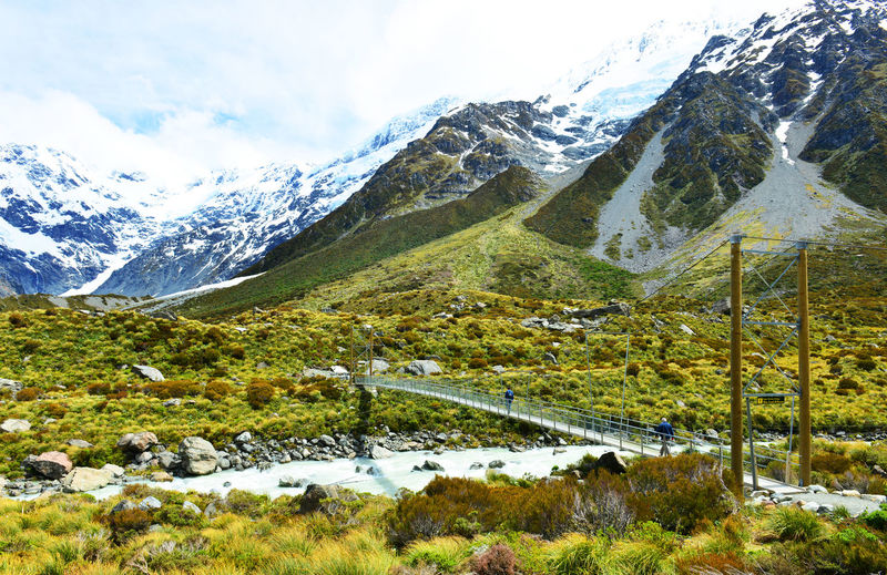 Footbridge by snowcapped mountains at mt cook national park