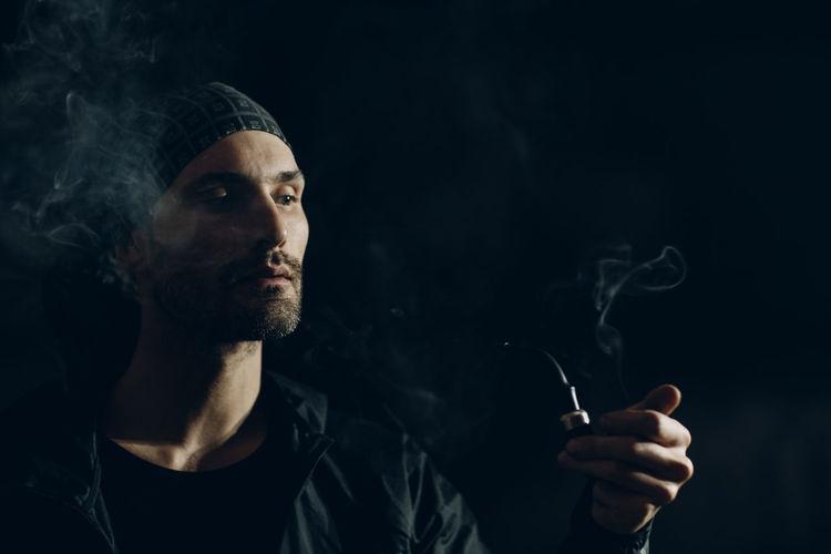 Man smoking pipe against black background