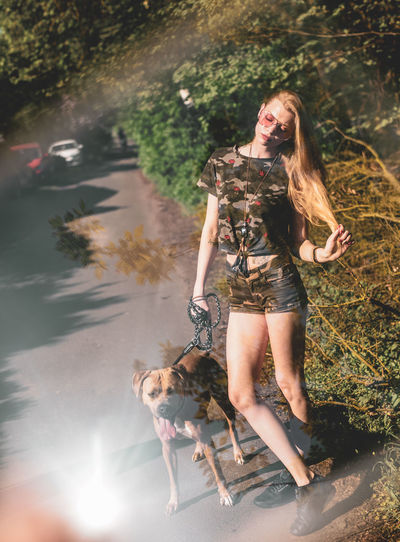 Young woman standing by dog on footpath