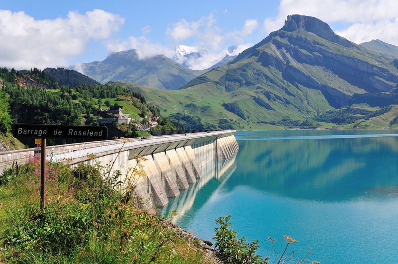 Scenic view of dam and mountains against sky