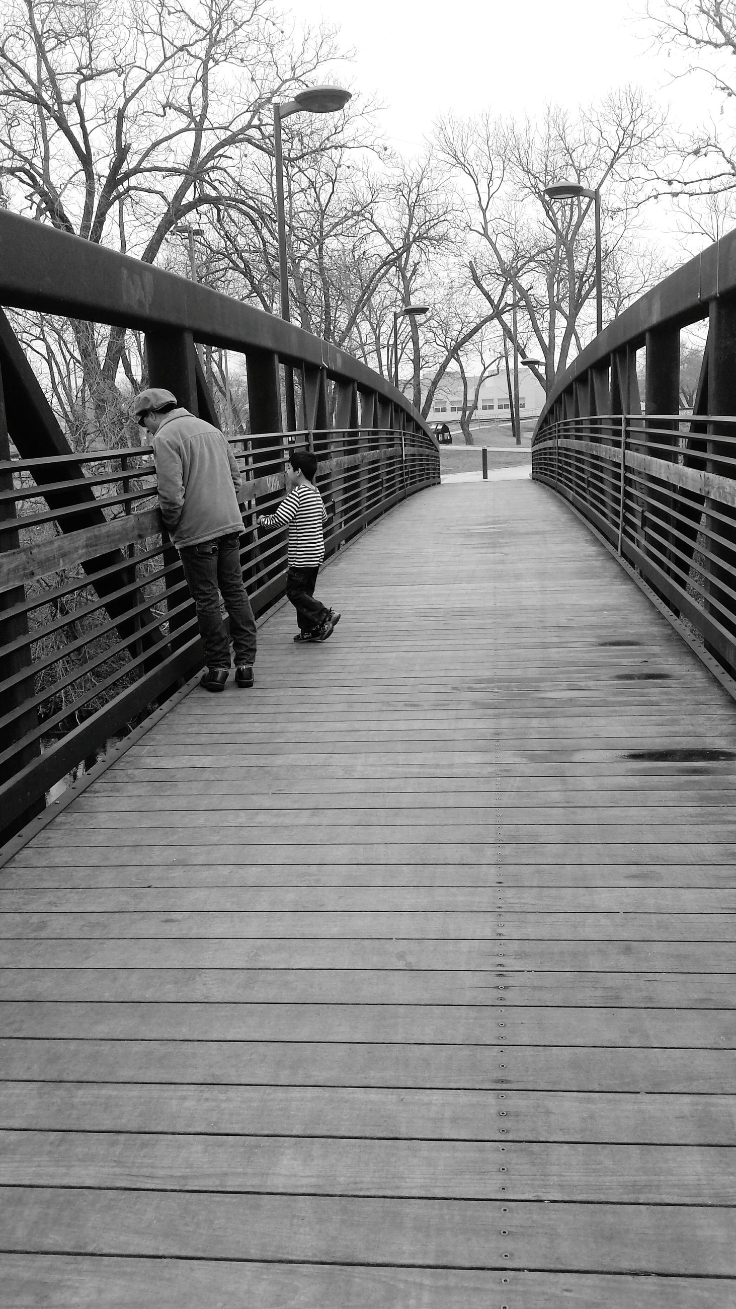 full length, railing, rear view, footbridge, the way forward, women, real people, bridge - man made structure, lifestyles, outdoors, walking, boardwalk, steps and staircases, day, one person, connection, steps, staircase, wood paneling, elevated walkway, people, sky, adult