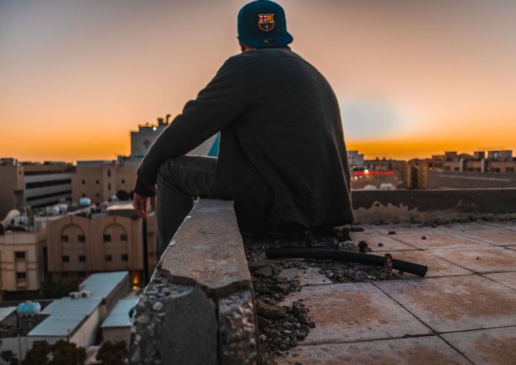 Rear view of man standing by buildings against sky during sunset