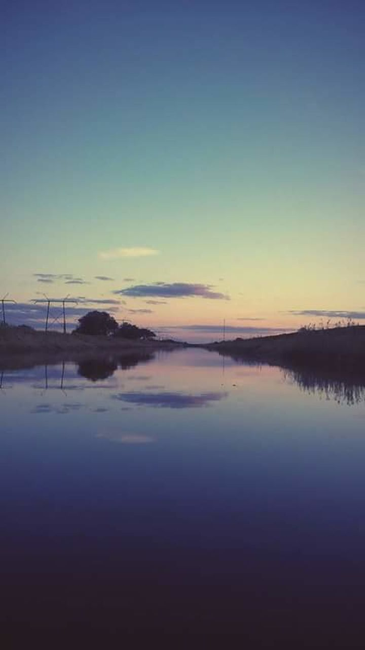 tranquility, tranquil scene, reflection, sunset, water, nature, beauty in nature, scenics, sky, no people, outdoors, silhouette, lake, idyllic, waterfront, blue, day