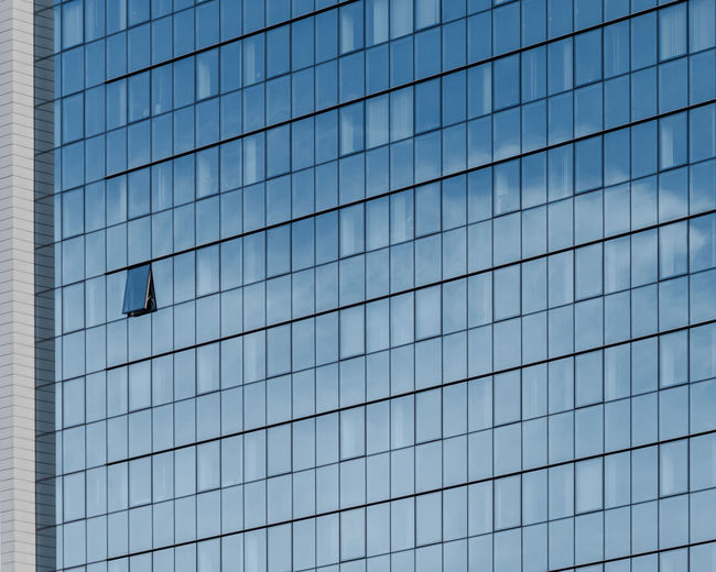 Low angle view of glass building against clear sky