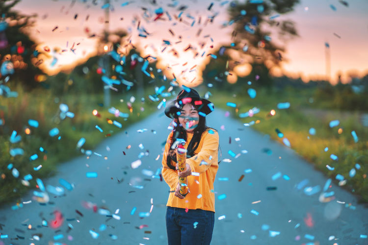 Cheerful woman with colorful confetti standing on road during sunset