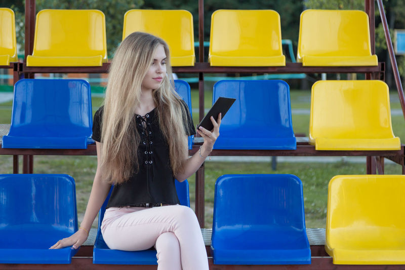 Young woman using digital tablet while sitting on chair