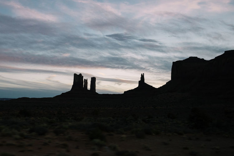 Silhouette Rock Formations Against Sky During Sunset