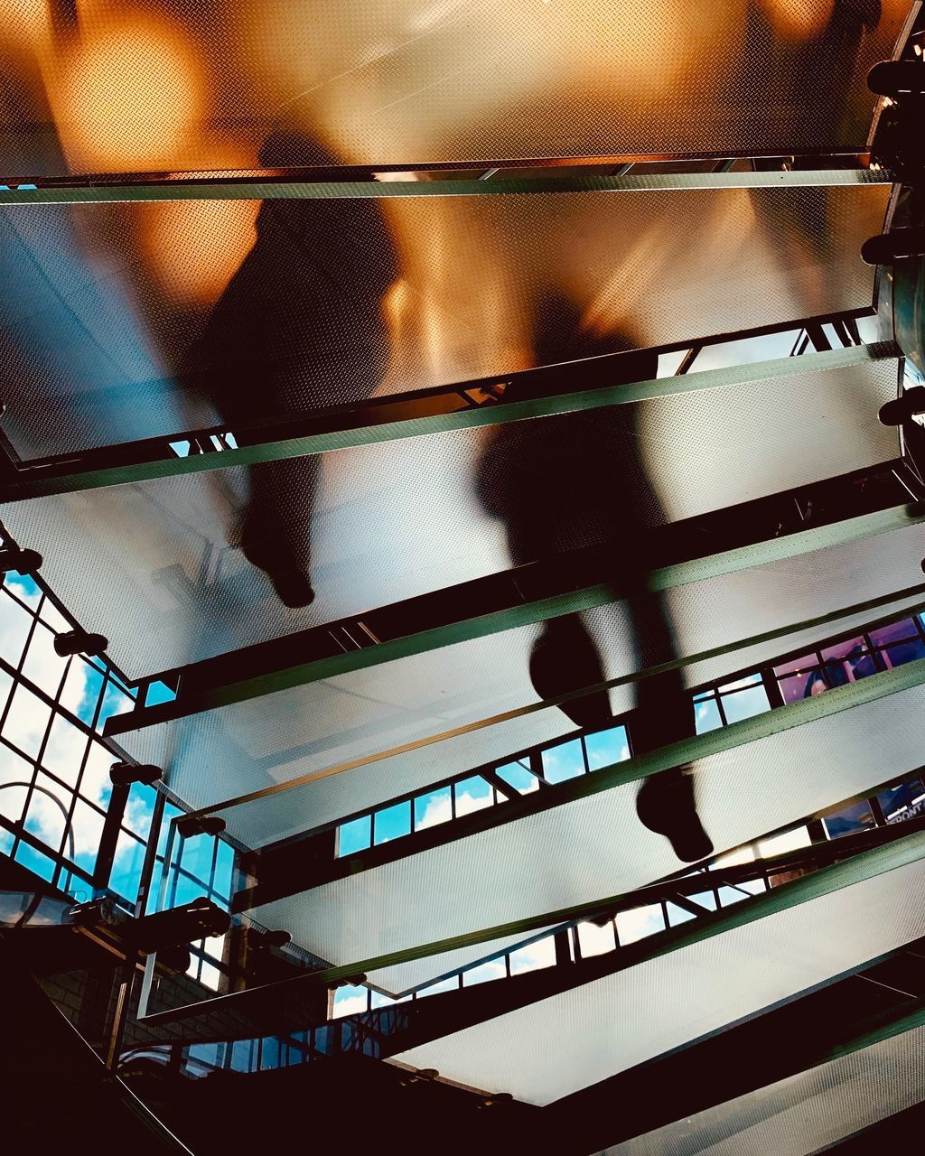 indoors, low angle view, architecture, real people, day, built structure, glass - material, illuminated, sunlight, ceiling, staircase, railing, shadow, lifestyles
