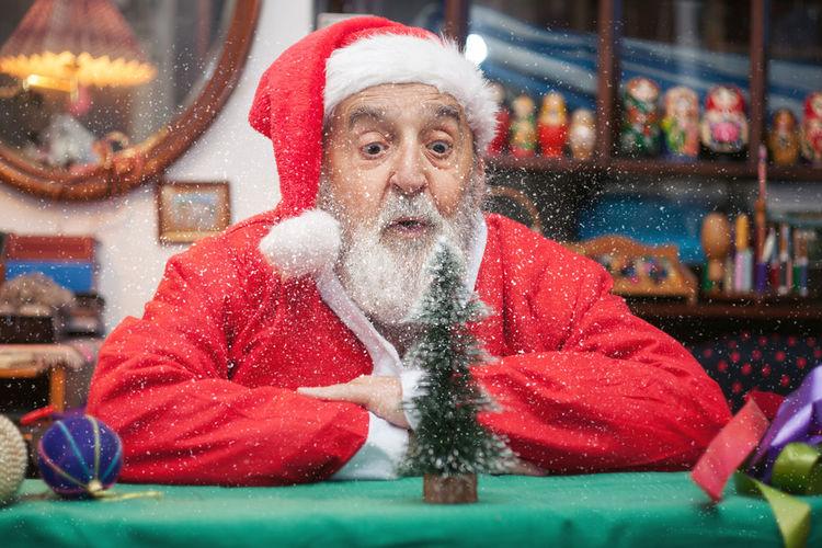 Senior Man In Santa Claus Costume Sitting At Home
