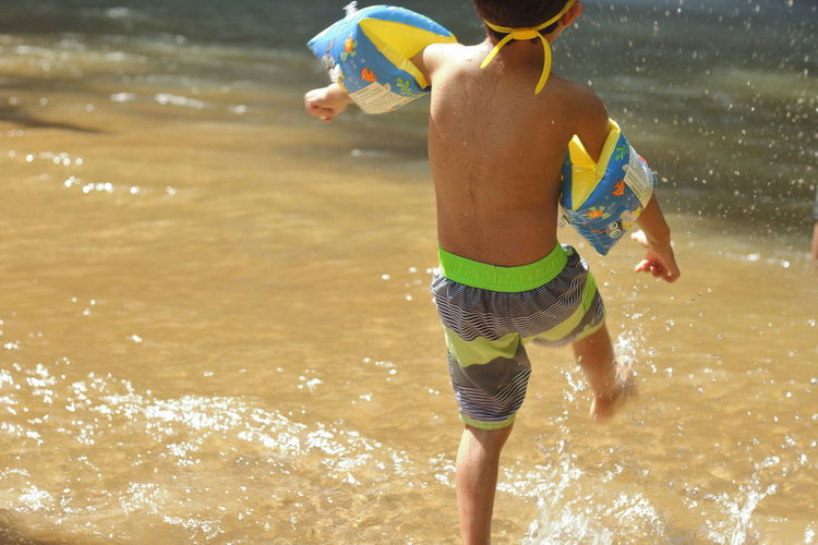 Rear View Of Shirtless Boy With Water Wings Playing In River