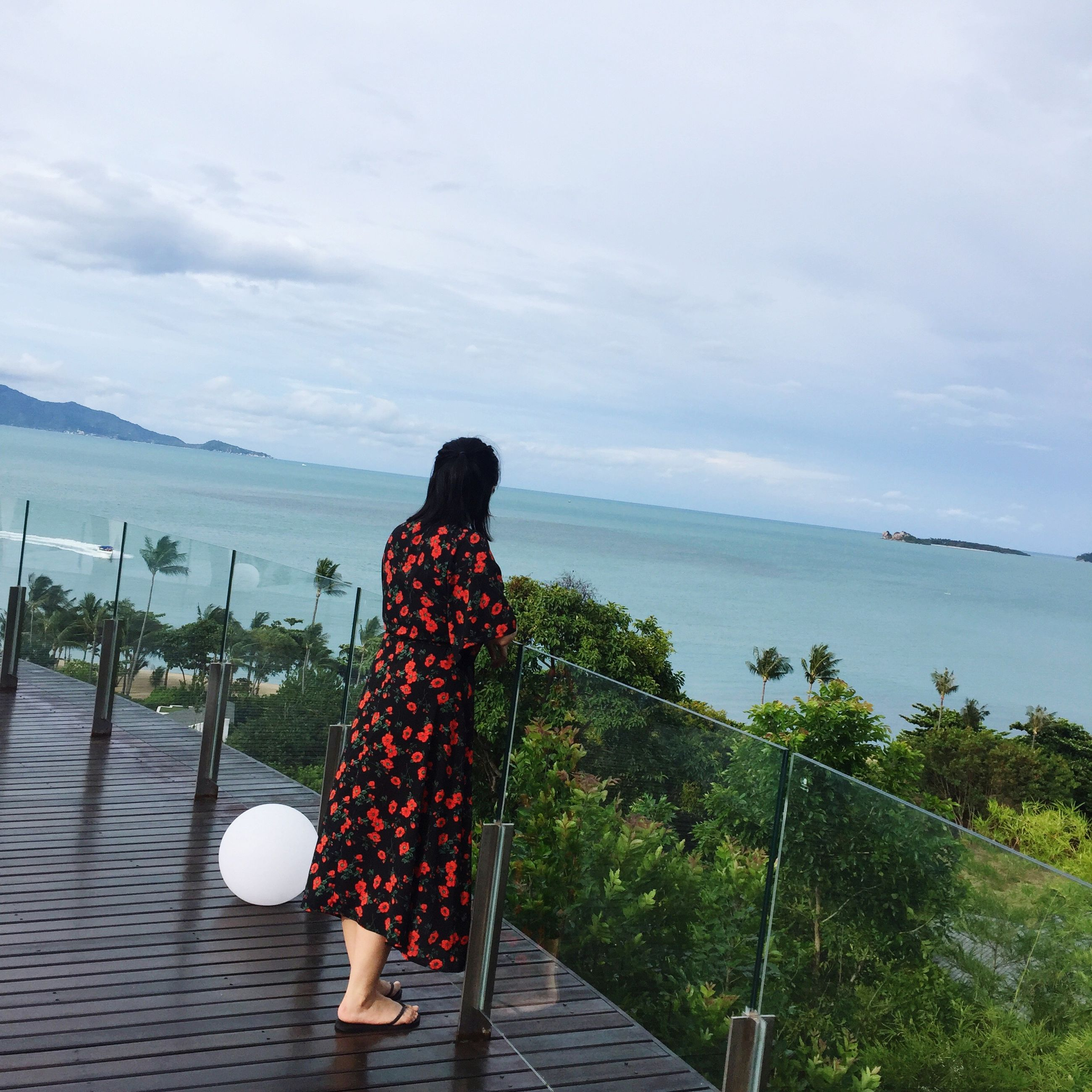 sea, rear view, water, sky, person, idyllic, tranquil scene, scenics, remote, tranquility, railing, day, casual clothing, getting away from it all, cloud, long hair, solitude, vacations, calm, cloud - sky, nature, carefree, beauty in nature, ocean, outdoors, tourism, coastline