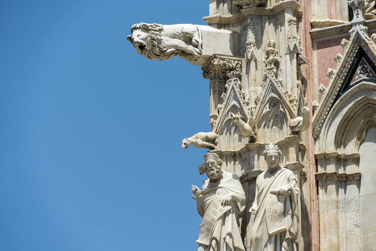 Shot in the city of Siena, Italy Ancient Civilization Architectural Column Architecture Art And Craft Belief Building Exterior Built Structure Clear Sky Craft Creativity Day Gargoyle History Human Representation Low Angle View Male Likeness No People Ornate Religion Representation Sculpture Sky Statue The Past