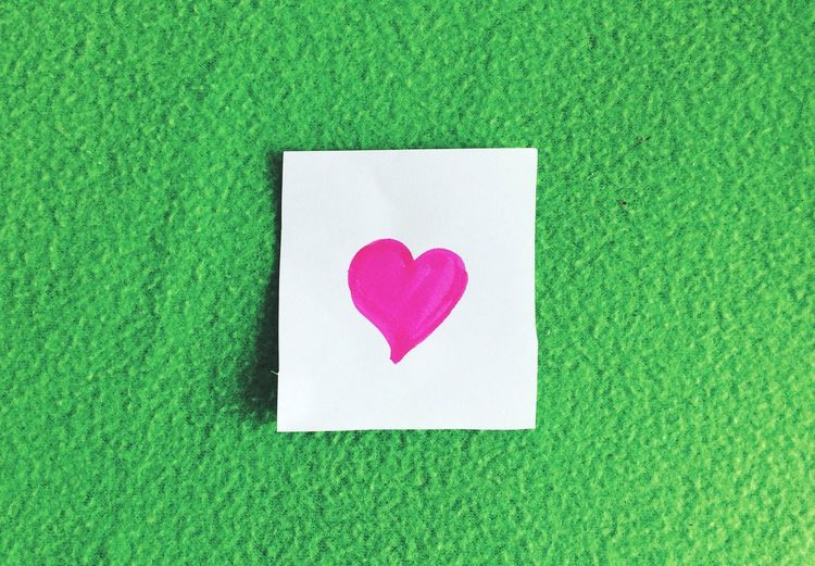 Close-up of white paper with heart shape on green wall