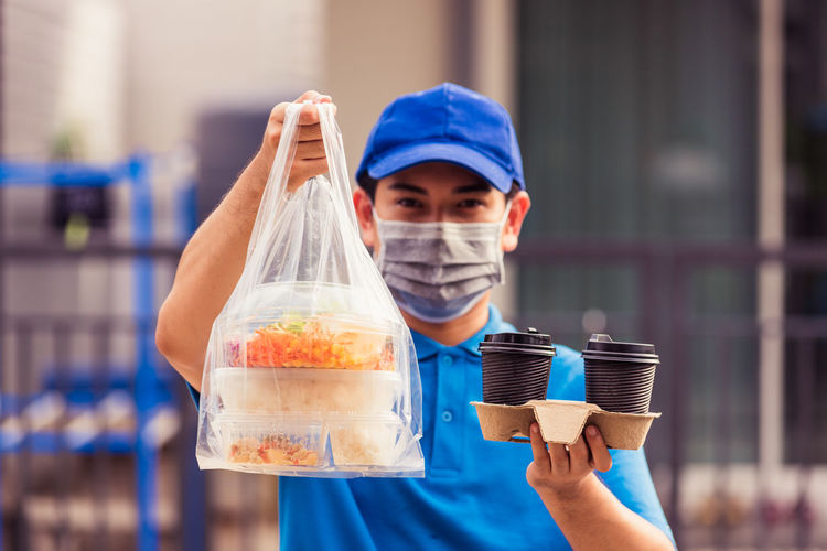 Delivery man in wearing face mask making grocery giving rice food boxes plastic bags and coffee