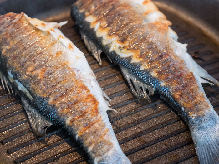 Whole sea bass fish cooking on hot grill pan Cooking Cuisine Mediterranean  Sea Bass Barbecue Close-up Delicious Dinner Fish Food Food And Drink Freshness Gourmet Grill Grilled Healthy Pan Preparing Food Ready-to-eat Restaurant Seafood Whole