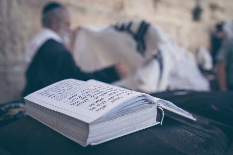 This is a jewish book in front of the wailing wall in Jerusalem. Publication Book Focus On Foreground People Men Education Religion Belief Paper Real People Spirituality Expertise Table Indoors  Place Of Worship Close-up Adult Studying Wailing Wall Jerusalem