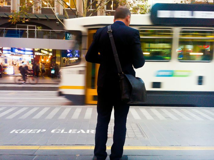 Rear view of man standing at subway station