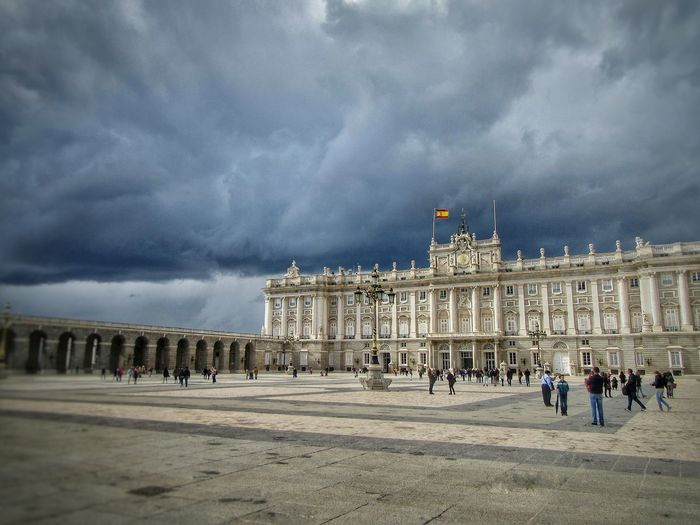 People in town square against cloudy sky