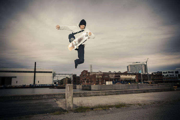 Man jumping in city against sky