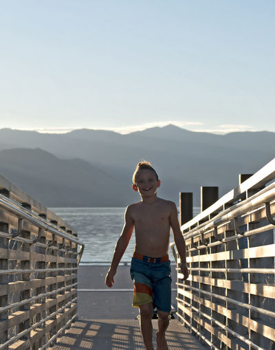 Full length portrait of shirtless boy walking on footbridge at beach against sky