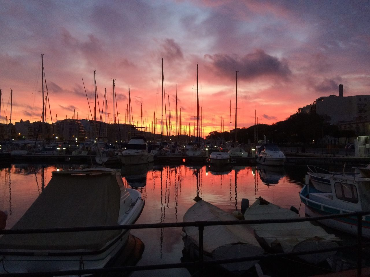Sailboats Moored At Harbor Against Sky During Sunset