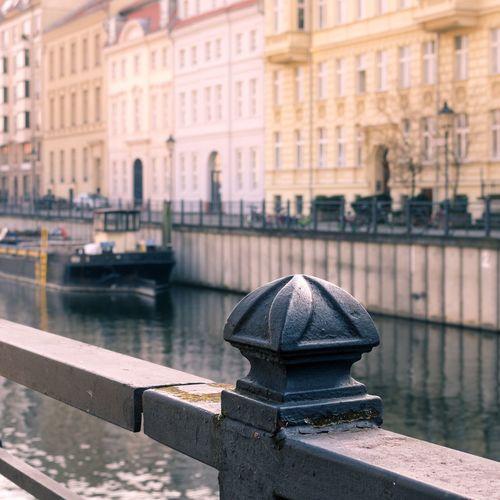 Boat in river against buildings in city