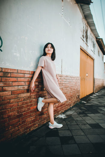 Full length portrait of woman standing against wall