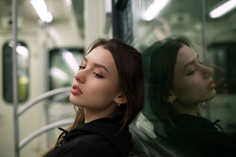 Young woman looking away while traveling in train