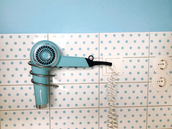 Blue vintage hair dryer at pattern wall