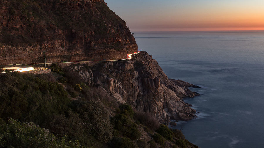 Light Trails On Mountain Road By Sea During Sunset