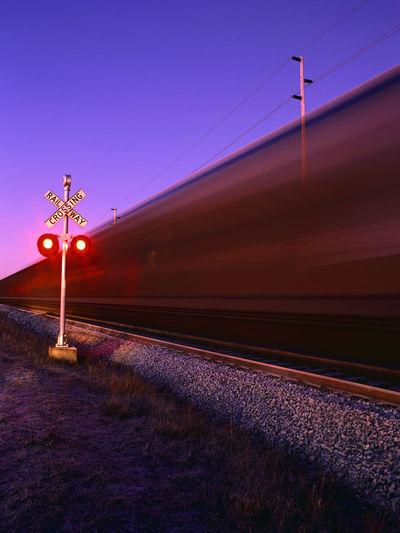 Illuminated railroad tracks by speeding train against clear sky